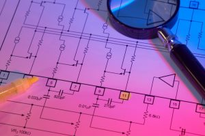 magnifying glass sitting on top of electrical blueprints