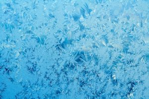 Beautiful frost pattern on a window in blue tones. Can be used as a winter / holiday background.