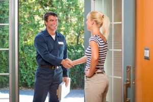 Repairman in uniform and clipboard greeting a housewife at the front door.