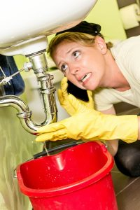 woman looking under sink in panic