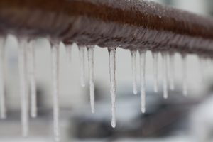 Icicles hanging from a brown pipe. Frozen water and metal surface, winter time concept. selective focus shallow depth of field photo