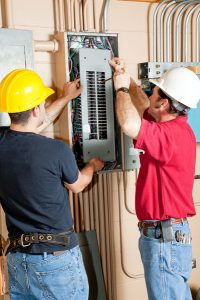 Two electricians working on electrical panel