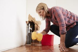 woman-wiping-up-water-from-burst-pipe-with-sponge