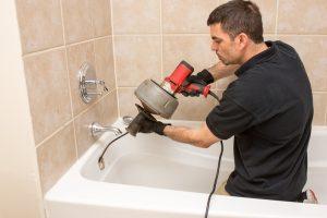 plumber-unclogging-drain-in-bathtub