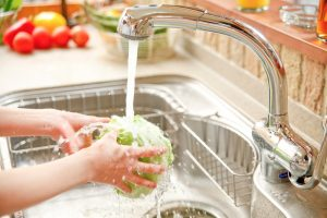 hands-washing-head-of-lettuce-over-drain-in-kitchen-sink