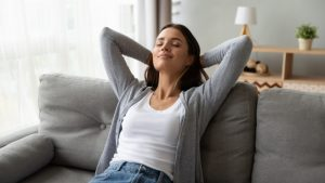 woman-looking-comfortable-in-home-leaning-back-on-couch-with-eyes-closed