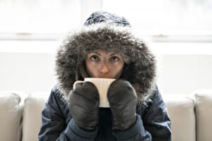 woman-in-parka-huddled-on-couch-drinking-of-of-mug