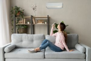 woman-sitting-on-couch-using-remote-to-turn-on-ductless-air-handler